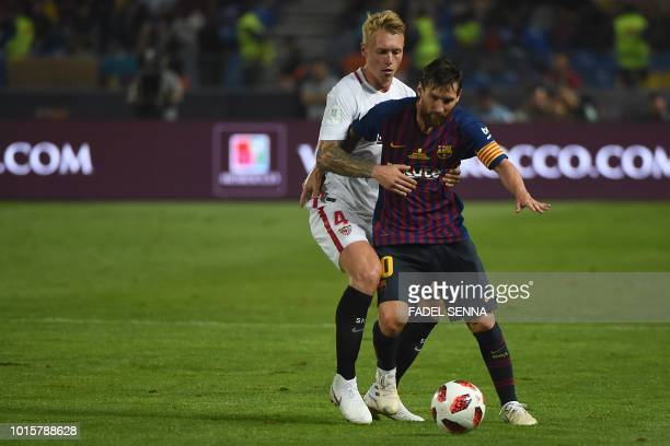 Barcelona's Argentinian forward Lionel Messi is fouled by Sevilla's Danish defender Simon Kjaer during the Spanish Super Cup final between Sevilla FC...
