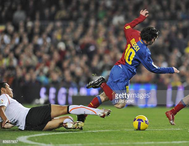 FC Barcelona's Argentinian forward Lionel Messi is tackeld by Valencia's Dutch center Hedwiges Maduro during their Spanish League football match on...