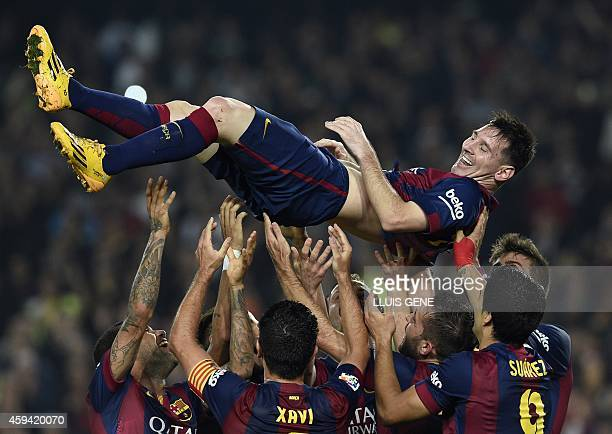 Barcelona's Argentinian forward Lionel Messi is thrown into the air by his teammates as they celebrate his new record after he scored during the...
