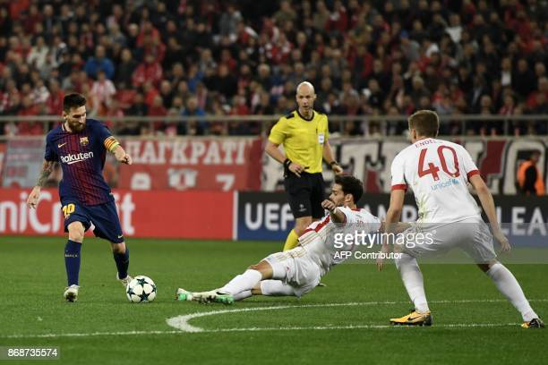 Barcelona's Argentinian forward Lionel Messi kicks the ball next to Olympiakos' Spanish defender Alberto Botia and Olympiakos' Belgian defender Bjorn...