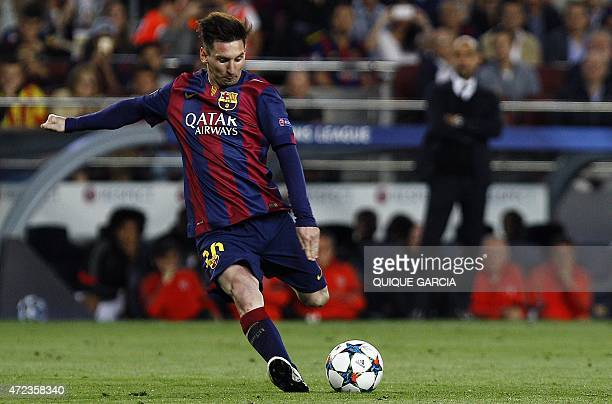 Barcelona's Argentinian forward Lionel Messi kicks the ball on a freekick while Bayern Munich's Spanish head coach Pep Guardiola looks on during the...