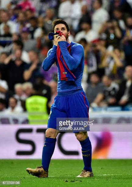 Barcelona's Argentinian forward Lionel Messi kisses his jersey after brandishing it to celebrate his goal during the Spanish league Clasico football...