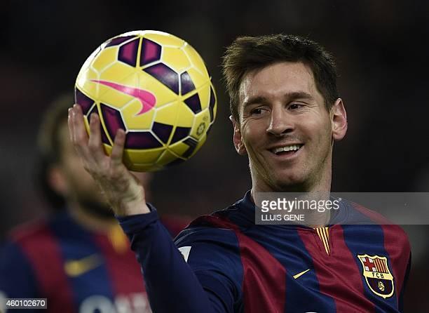 Barcelona's Argentinian forward Lionel Messi leaves the pitch with the ball after his hattrick after the Spanish league football match FC Barcelona...