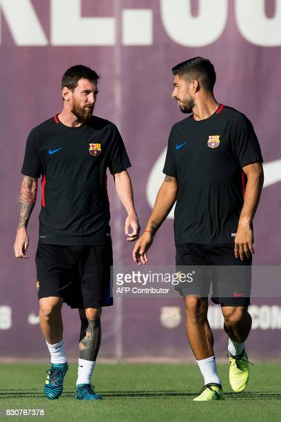 Barcelona's Argentinian forward Lionel Messi looks at Barcelona's Uruguayan forward Luis Suarez during a training session at the sports Center FC...