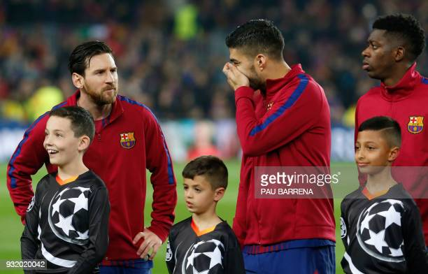 Barcelona's Argentinian forward Lionel Messi looks at Barcelona's Uruguayan forward Luis Suarez beside Barcelona's French forward Ousmane Dembele...