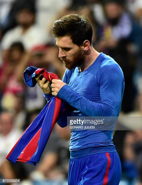 Barcelona's Argentinian forward Lionel Messi looks at his jersey after brandishing it to celebrate his goal during the Spanish league Clasico...