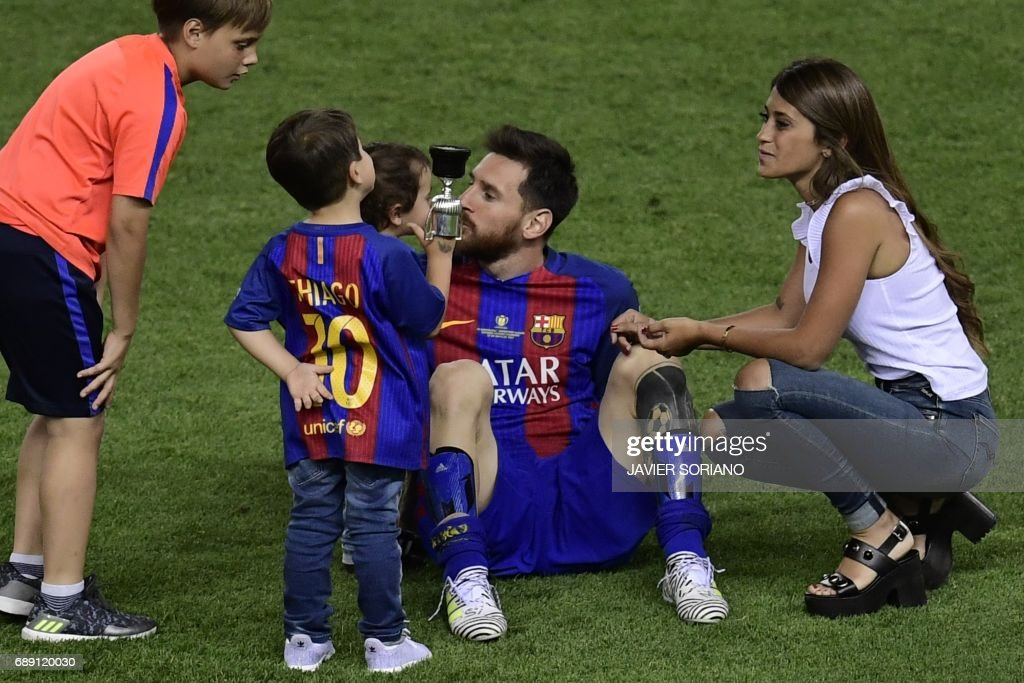 Barcelona's Argentinian forward Lionel Messi (C) looks at his sons past his wife Antonella Roccuzzo (R) at the end of the Spanish Copa del Rey (King's Cup) final football match FC Barcelona vs Deportivo Alaves at the Vicente Calderon stadium in Madrid on May 27, 2017. Barcelona won 3-1. /