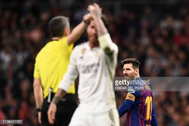 TOPSHOT Barcelona's Argentinian forward Lionel Messi looks at Real Madrid's Spanish defender Sergio Ramos during the Spanish league football match...
