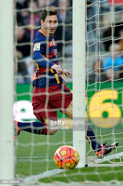 Barcelona's Argentinian forward Lionel Messi looks at the ball as he scores a goal during the Spanish league football match FC Barcelona vs Granada...