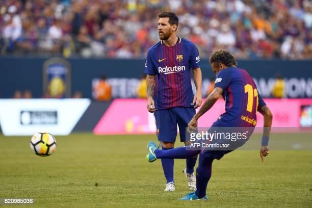 TOPSHOT Barcelona's Argentinian forward Lionel Messi looks on as Barcelona's Brazilian forward Neymar kicks the all during the International...