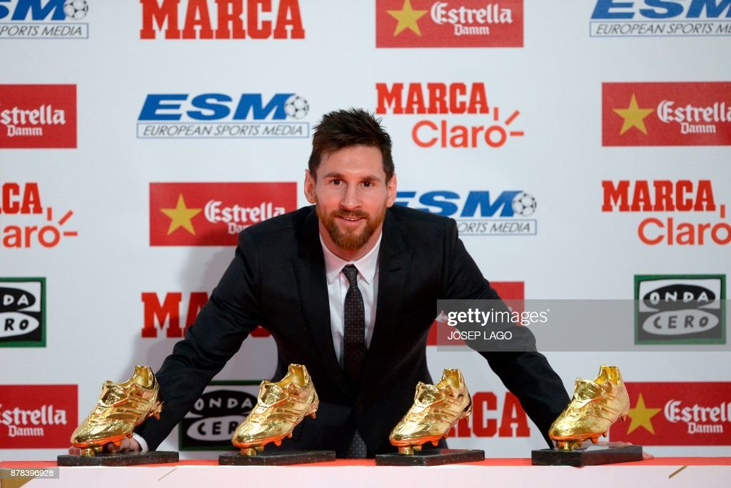TOPSHOT - Barcelona's Argentinian forward Lionel Messi poses with his four Golden Shoe awards after receiving the 2017 European Golden Shoe honoring the year's leading goalscorer during a ceremony at the Antigua Fabrica Estrella Damm in Barcelona on November 24, 2017. / AFP PHOTO / Josep LAGO