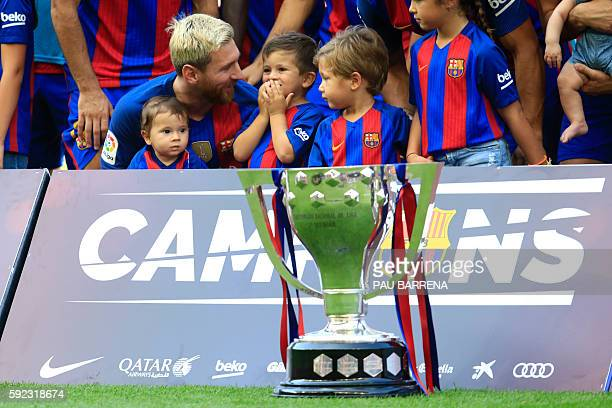 Barcelona's Argentinian forward Lionel Messi poses with his sons Thiago and Mateoand the La Liga 201516 trophy before the Spanish league football...