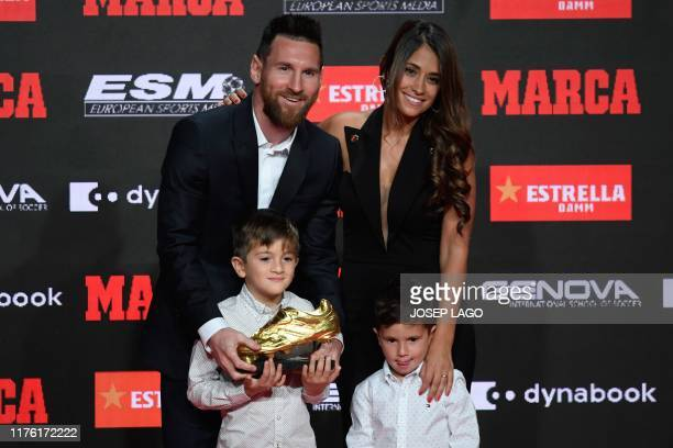 Barcelona's Argentinian forward Lionel Messi poses with his wife Antonella Roccuzzo and his sons Thiago and Mateo after receiving his sixth Golden...