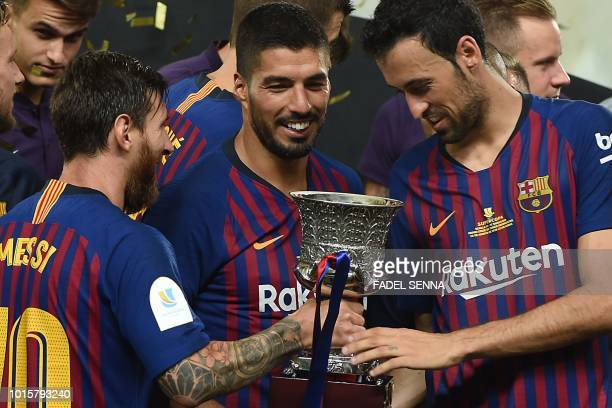 Barcelona's Argentinian forward Lionel Messi presents the cup to Barcelona's Spanish midfielder Sergio Busquets next to Barcelona's Uruguayan forward...