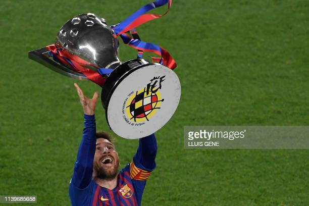 Barcelona's Argentinian forward Lionel Messi raises La Liga trophy as he celebrates becoming La Liga champions after winning the Spanish League...