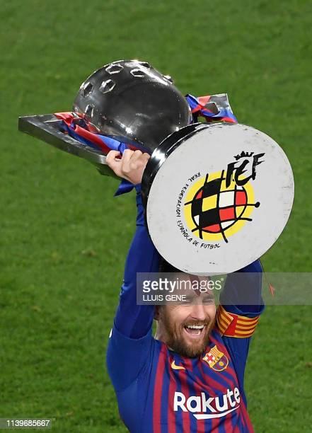 Barcelona's Argentinian forward Lionel Messi raises La Liga trophy as he celebrates becoming La Liga champions after winning the Spanish League...