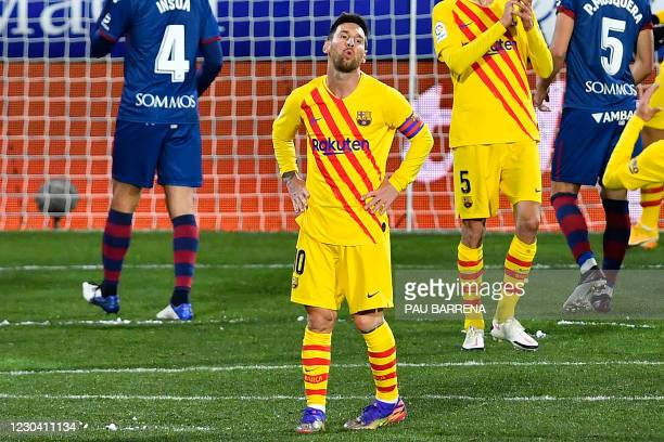Barcelona's Argentinian forward Lionel Messi reacts after missing a goal opportunity during the Spanish League football match between Huesca and...
