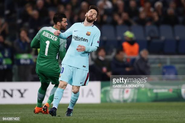 FC Barcelona's Argentinian forward Lionel Messi reacts next to AS Roma's Brazilian goalkeeper Alisson Becker during the UEFA Champions League...