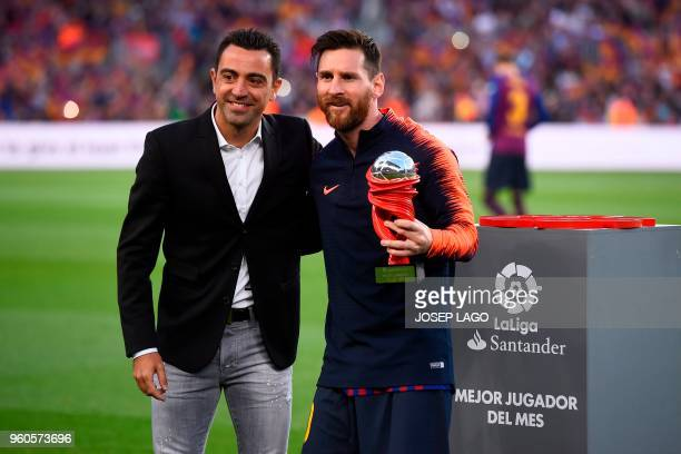 Barcelona's Argentinian forward Lionel Messi receives the player of the month trophy from Barcelona's former Spanish midfielder Xavi before the...