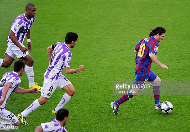 Barcelona's Argentinian forward Lionel Messi runs for the ball in front of Valladolid's players during a Spanish League football match at the Camp...