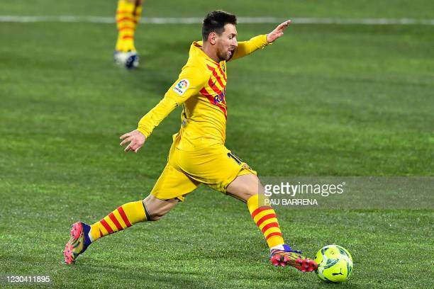 Barcelona's Argentinian forward Lionel Messi runs with the ball during the Spanish League football match between Huesca and Barcelona at the El...