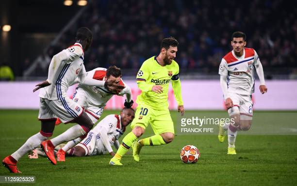 Barcelona's Argentinian forward Lionel Messi runs with the ball next to Lyon's French defender Ferland Mendy Lyon's French midfielder Lucas Tousart...