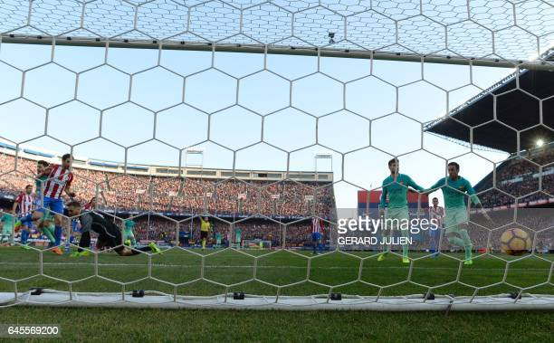 Barcelona's Argentinian forward Lionel Messi scores a goal beside Atletico Madrid's Slovenian goalkeeper Jan Oblak during the Spanish league football...