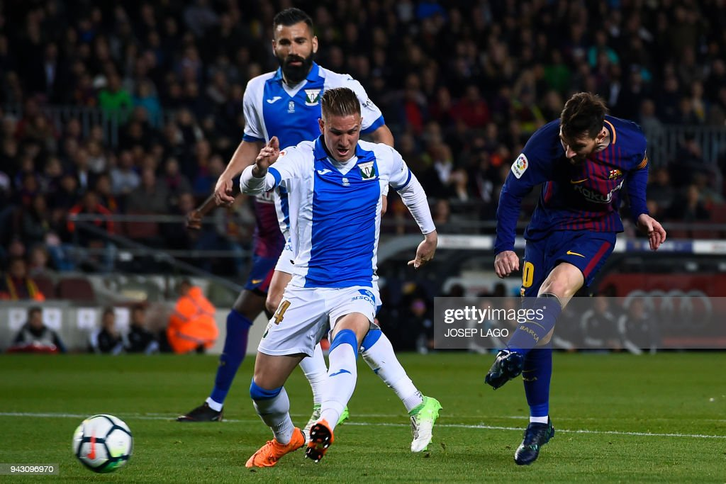 Barcelona's Argentinian forward Lionel Messi (R) scores a goal past Leganes' Spanish defender Raul Garcia (C) and Leganes' Greek defender Dimitrios Siovas (L) during the Spanish league football match between Barcelona and Leganes at the Camp Nou stadium in Barcelona on April 7, 2018. / AFP PHOTO / Josep LAGO