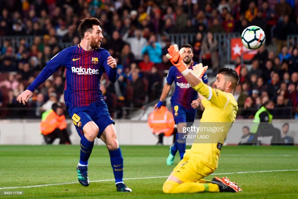Barcelona's Argentinian forward Lionel Messi (L) scores a third goal past Leganes' Spanish goalkeeper Pichu Cuellar during the Spanish league football match between FC Barcelona and Club Deportivo Leganes SAD at the Camp Nou stadium in Barcelona on April 7, 2018. / AFP PHOTO / Josep LAGO