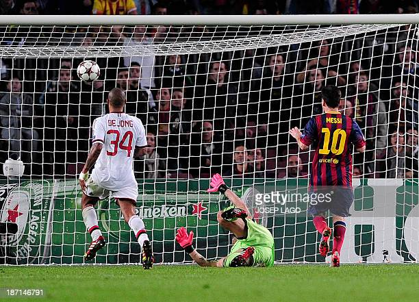 Barcelona's Argentinian forward Lionel Messi scores against AC Milan's goalkeeper Christian Abbiati and AC Milan's midfielder Nigel de Jong during...