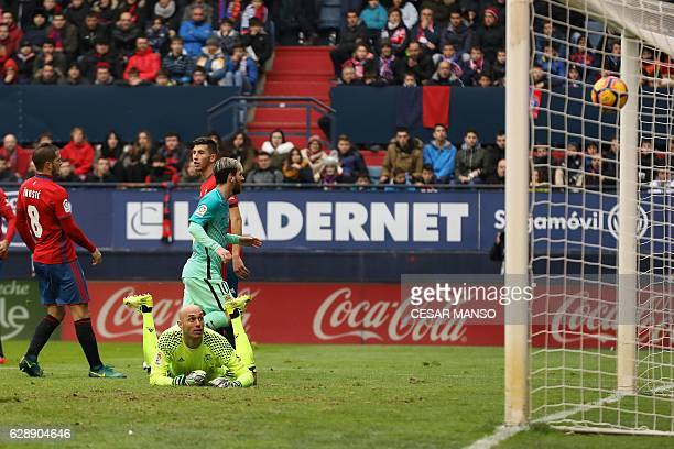 Barcelona's Argentinian forward Lionel Messi scores during the Spanish league football match CA Osasuna vs FC Barcelona at the Reyno de Navarra...