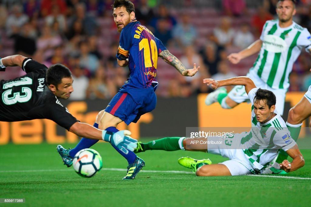 TOPSHOT - Barcelona's Argentinian forward Lionel Messi (C) scores during the Spanish league footbal match FC Barcelona vs Real Betis at the Camp Nou stadium in Barcelona on August 20, 2017. /