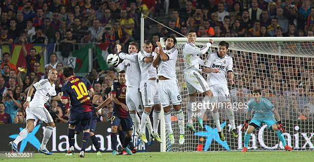 Barcelona's Argentinian forward Lionel Messi scores on a freekick during the Spanish League clasico football match FC Barcelona vs Real Madrid at the...
