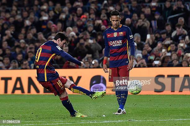 Barcelona's Argentinian forward Lionel Messi shoots a free kick to score a goal next to Barcelona's Brazilian forward Neymar during the Spanish...