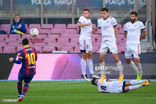 Barcelona's Argentinian forward Lionel Messi shoots the ball during the Spanish League football match between FC Barcelona and CA Osasuna at the Camp...