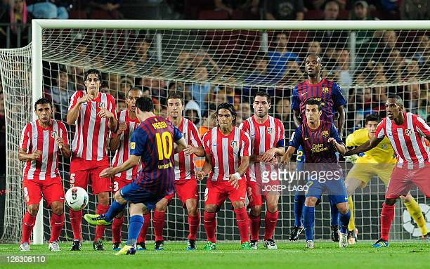 Barcelona's Argentinian forward Lionel Messi shoots the ball on a freekick during the Spanish league football match FC Barcelona vs Atletico de...
