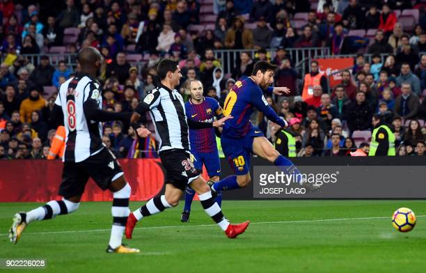 Barcelona's Argentinian forward Lionel Messi shoots to score a goal during the Spanish league football match FC Barcelona vs Levante UD at the Camp...