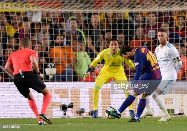 Barcelona's Argentinian forward Lionel Messi shoots to score a goal during the Spanish league football match between FC Barcelona and Real Madrid CF...