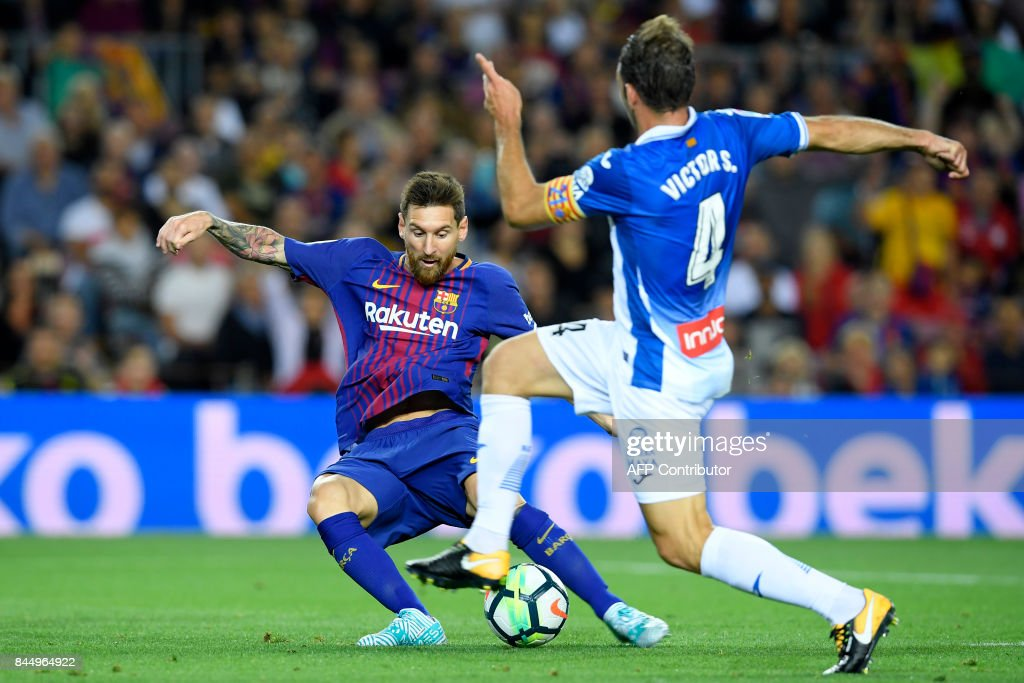 Barcelona's Argentinian forward Lionel Messi (L) shoots to score next to Espanyol's midfielder Victor Sanchez during the Spanish Liga football match Barcelona vs Espanyol at the Camp Nou stadium in Barcelona on September 9, 2017. /