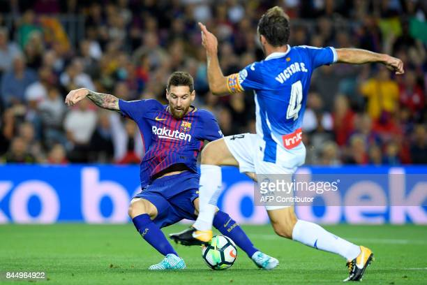 Barcelona's Argentinian forward Lionel Messi shoots to score next to Espanyol's midfielder Victor Sanchez during the Spanish Liga football match...