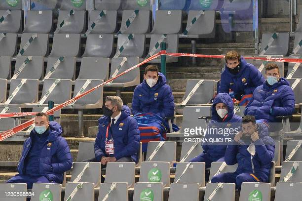 Barcelona's Argentinian forward Lionel Messi sits with substitutes on the grandstands during the Spanish Super Cup semi final football match between...