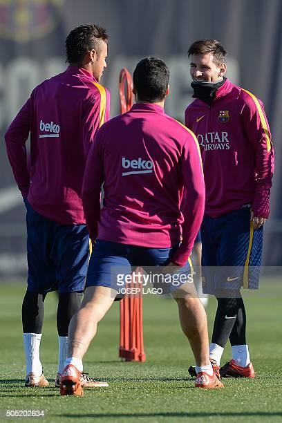 Barcelona's Argentinian forward Lionel Messi smiles to Barcelona's Uruguayan forward Luis Suarez and Barcelona's Brazilian forward Neymar da Silva...