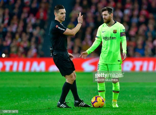 Barcelona's Argentinian forward Lionel Messi speaks with Spanish referee Carlos del Cerro Grande during the Spanish league football match Athletic...