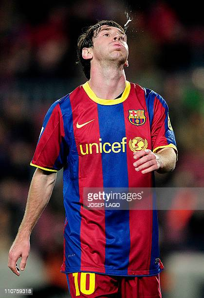 Barcelona's Argentinian forward Lionel Messi spits during the Copa del Rey football match FC Barcelona vs Real Betis on January 12 2011 at the Camp...