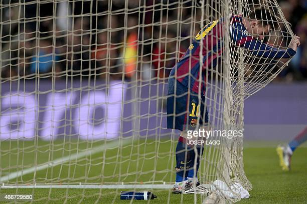 Barcelona's Argentinian forward Lionel Messi stands inside the goal net during the UEFA Champions League round of 16 football match FC Barcelona vs...