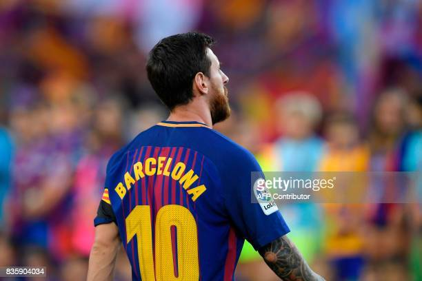 Barcelona's Argentinian forward Lionel Messi stands with his jersey reading 'Barcelona' instead of his name to pay tribute to the victims of the...