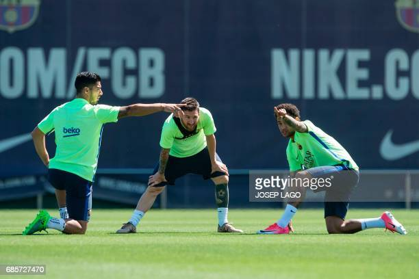 Barcelona's Argentinian forward Lionel Messi stretches as Barcelona's Uruguayan forward Luis Suarez and Barcelona's Brazilian forward Neymar gesture...