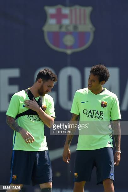 Barcelona's Argentinian forward Lionel Messi talks with Barcelona's Brazilian forward Neymar during a training session at the Sports Center FC...