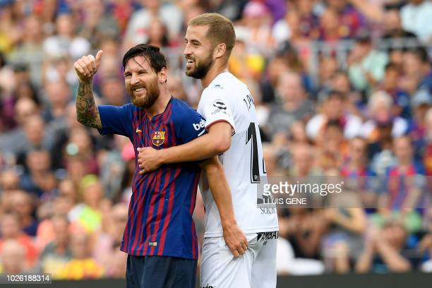 Barcelona's Argentinian forward Lionel Messi thumbs up beside SD Huesca's Spanish defender Jorge Pulido during the Spanish league football match...