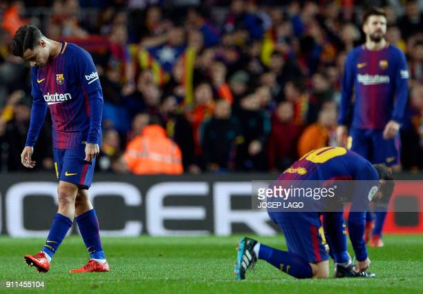 Barcelona's Argentinian forward Lionel Messi ties his shoelaces beside Barcelona's Brazilian midfielder Philippe Coutinho following the opening goal...